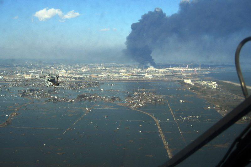 Aerial view of seaside port inundated by water, huge column of black smoke in distance.