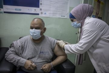 Iraqi refugee Ziad receives a dose of COVID-19 vaccine at the Irbid Vaccination Clinic in Jordan.