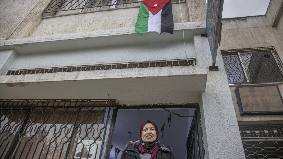 Raia AlKabashi stands under the flag of Jordan outside the health centre in Irbid where she received her COVID-19 vaccine.